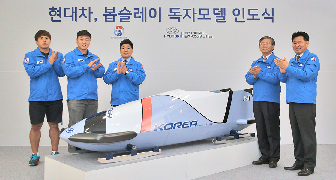 representatives wearing blue jackets standing and clapping next to Hyundai bobsled