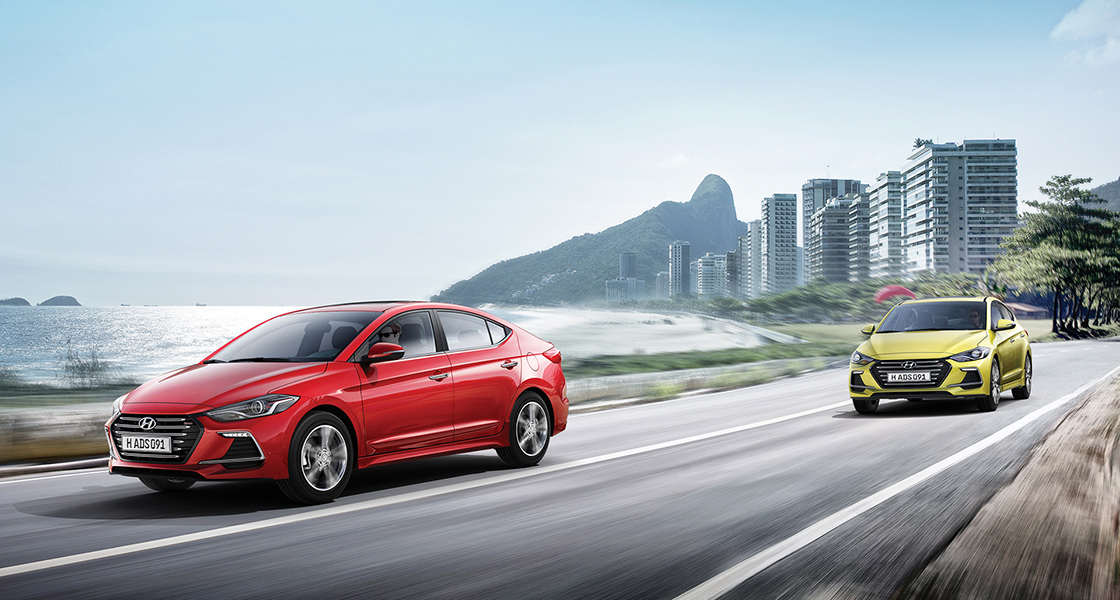 Left side front view of two Elantra Sport cars driving on the road with the city background