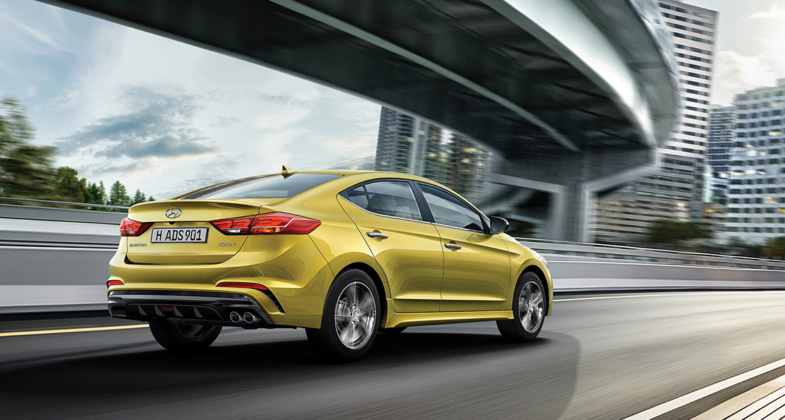 Right side rear view of yellow Elantra Sport driving on the road