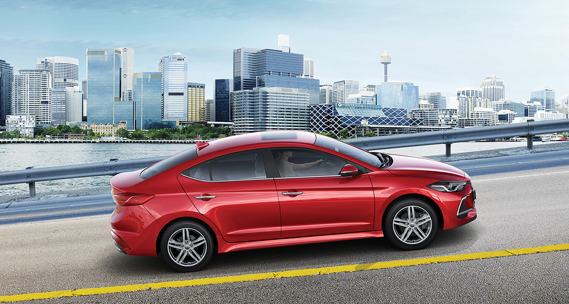 Side view of red Elantra Sport on the road with buildings background