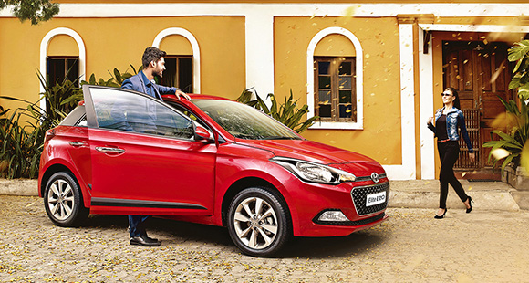 A man getting to the passenger's seat of red Elite i20 parked in front of yellow building