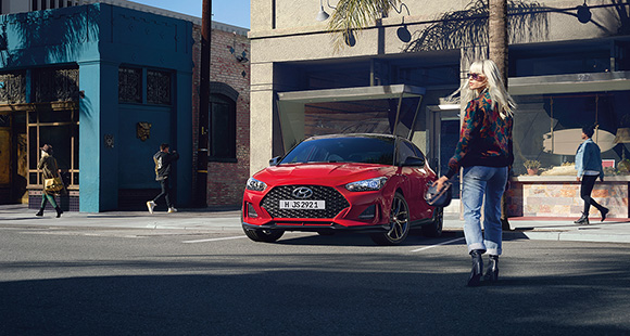 Red veloster next to a woman