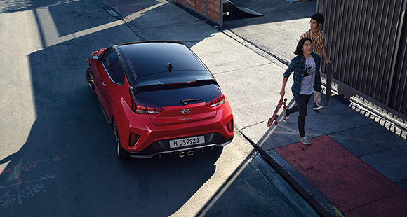 A woman and left side rear view of red veloster parking on the road