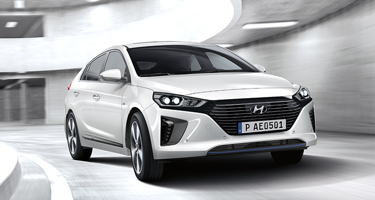 A driver approaching to the side of white Ioniq plug-in hybrid