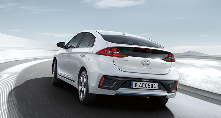 Side rear view of white Ioniq plug-in hybrid driving on the road.