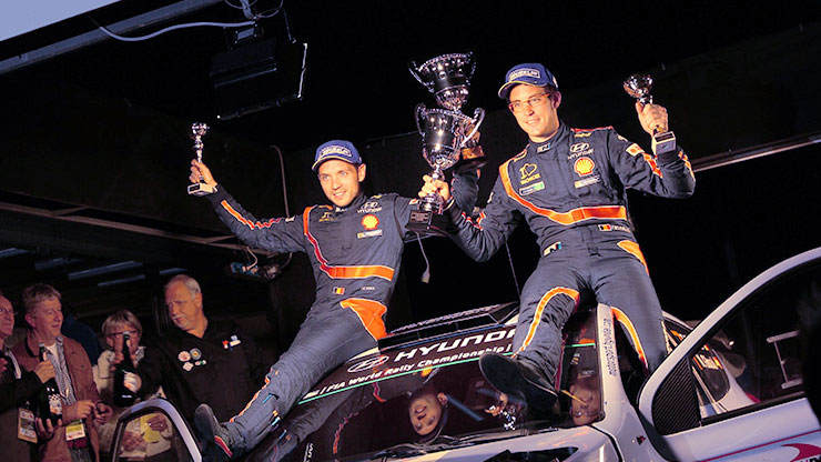 thierry neuville and nicolas gilsoul raises trophy and sits on the top of the car to celebrate