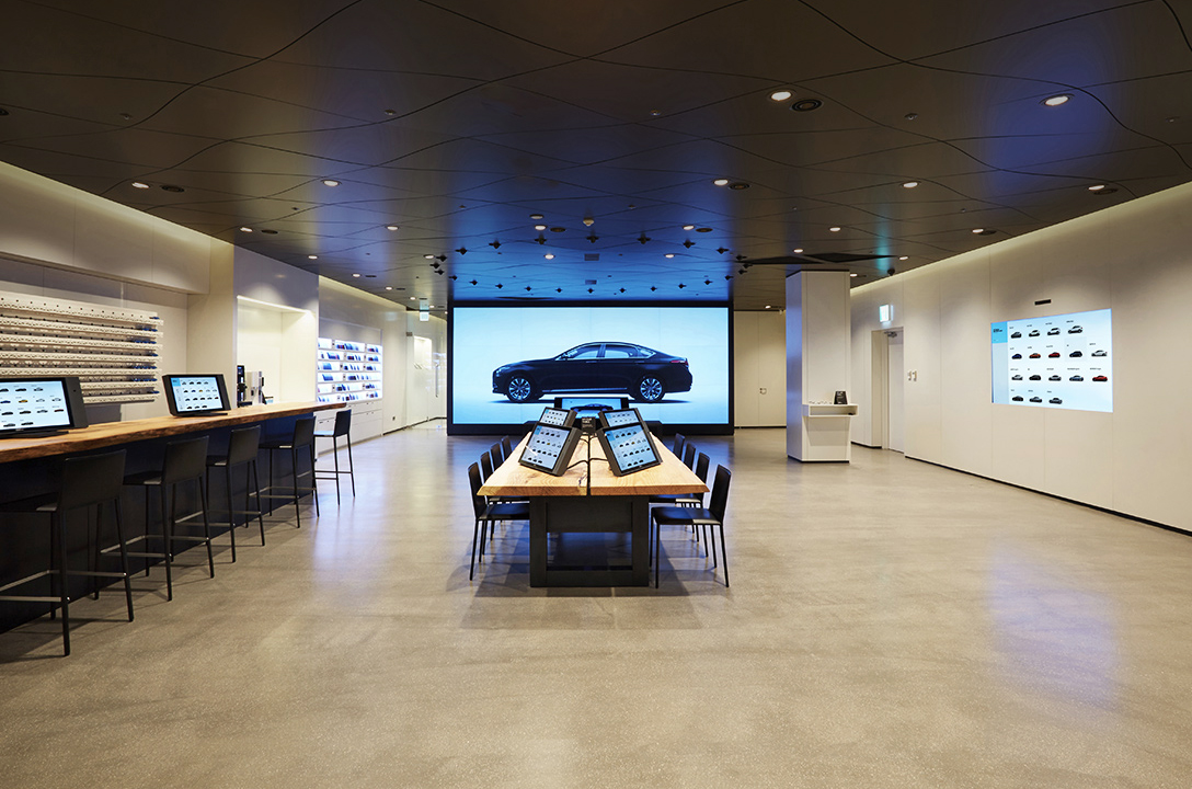 4 tablet PCs on the table and 2 screens on the walls are reflecting picture of cars at the Motorstudio Digital